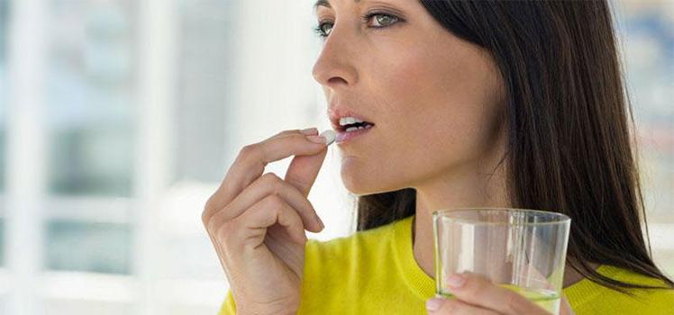 женщина пьёт таблетки